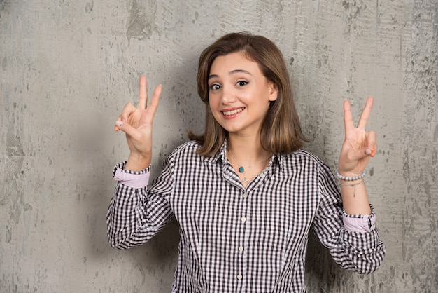 A pretty girl showing two fingers victory sign.