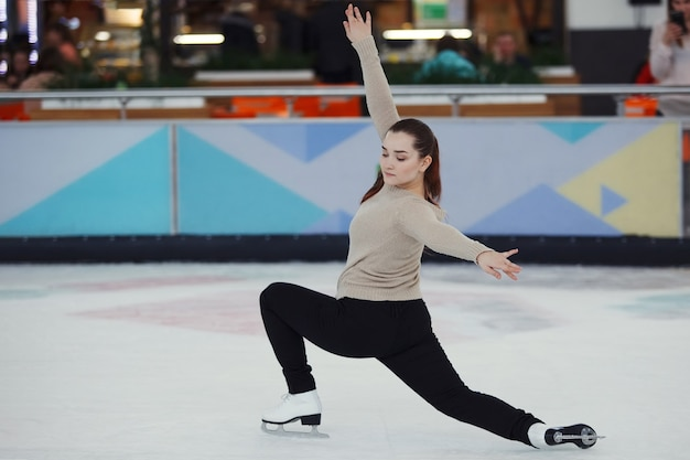 A pretty girl shows exercises in figure skating on ice indoors