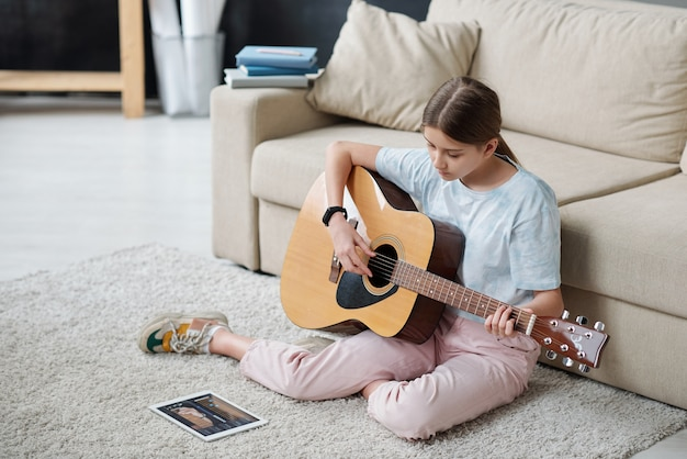 Pretty girl sitting on the floor by couch and learning to play guitar while looking at touchpad screen during online lesson