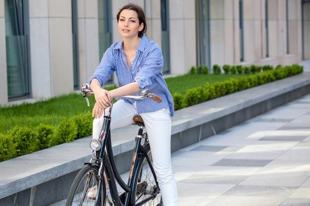 Красивая девушка сидит на велосипеде на улице Бесплатные Фотографии