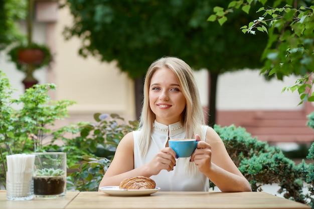 コーヒーを飲みながら、クロワッサンを食べて屋外カフェロッジに座っているきれいな女の子。