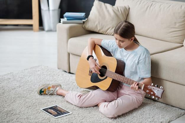 Красивая девушка сидит на полу у дивана и учится играть на гитаре, глядя на экран тачпада во время онлайн-урока