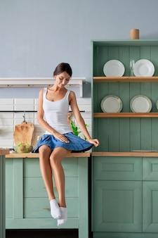 Красивая девушка сидит на столе в своей кухне и ждет завтрак