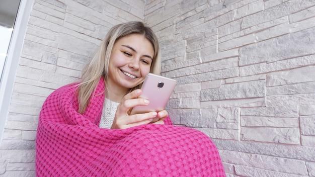 Красивая девушка сидит на подоконнике со смартфоном в руках. у нее длинные светлые волосы, она улыбается и смотрит в свой телефон.