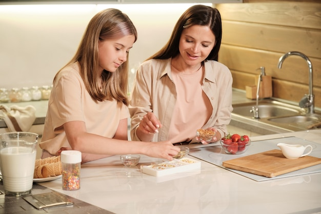 Pretty girl sprinkling ground nuts on top of homemade icecream in silicone forms while helping mother with preparation of yummy stuff