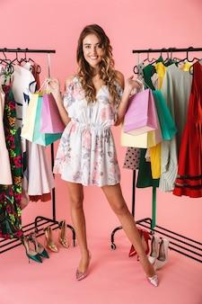 Красивая девушка стоит в магазине возле вешалки и держит разноцветные хозяйственные сумки, изолированные на розовом
