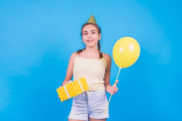 Pretty girl standing with gift box and balloons on blue wallpaper