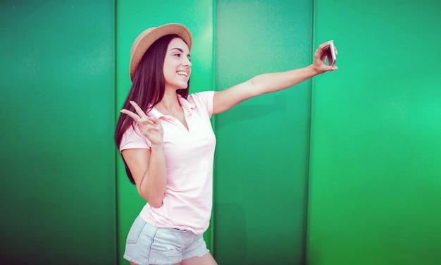 예쁜 여자가 서서 포즈를 취합니다. 그녀는 휴대전화를 손에 들고 셀카를 찍는다. 소녀는 조각 기호가 있습니다. 그녀는 그것을 그녀의 손가락으로 만들었습니다. 줄무늬와 녹색 배경에 고립.