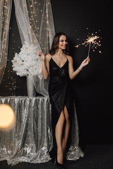 Bella ragazza si trova vicino a una decorazione in colore argento e guarda una stella filante