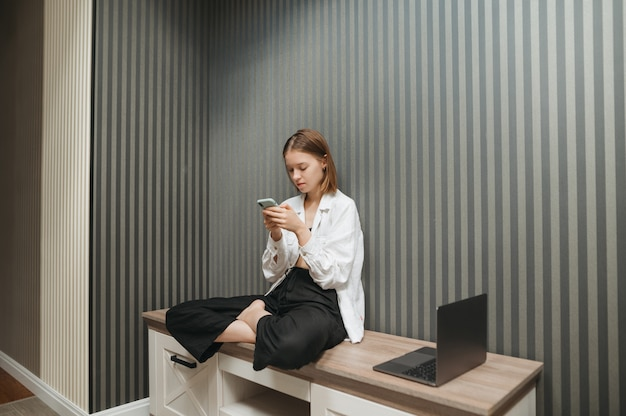 Pretty girl in stylish clothes sits on a bedside table at home in apartment and uses a smartphone