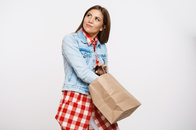 Pretty girl in stylish spring look holding brown paper bag