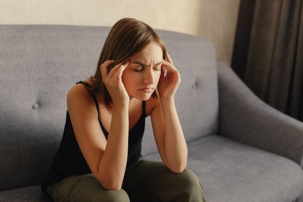 頭痛に苦しみ、こめかみに手を当て、痛みのために目を閉じているかわいい女の子。