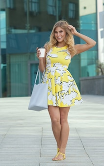 Pretty girl in summer dress on street with morning coffee