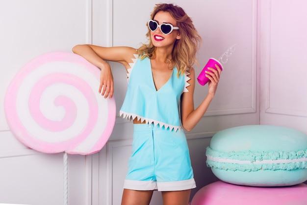 Ragazza graziosa in occhiali da sole con bella pelle e labbra, in posa in studio, bere succo di frutta o cocktail. indossa occhiali da sole a cuore vintage, elegante top in pelle blu.