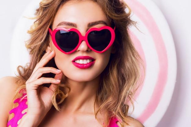 Ragazza graziosa in occhiali da sole con bella pelle e labbra, in posa in studio