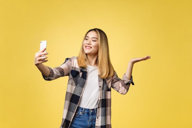 예쁜 여자는 그녀의 스마트 폰으로 자기 초상화를 가져가 라. 아시아 여자 selfie