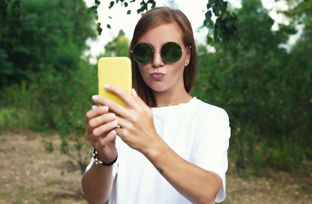 Красивая девушка делает автопортрет со своим смартфоном