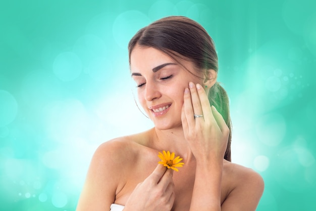 Pretty girl takes care her skin with yellow flower in hands isolated on white background. health care concept. body care concept. young woman with healthy skin.