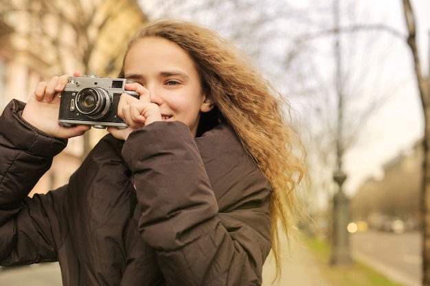 Pretty girl taking a photo with a camera