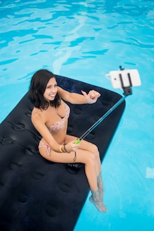 Pretty girl taking selfie photo on the phone with selfie stick and showing thumbs up gesture of good class on mattress in pool. view from above