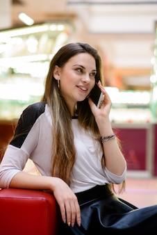 Красивая девушка разговаривает по телефону в торговом центре.