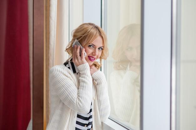 Красивая девушка разговаривает по телефону у окна, блондинка