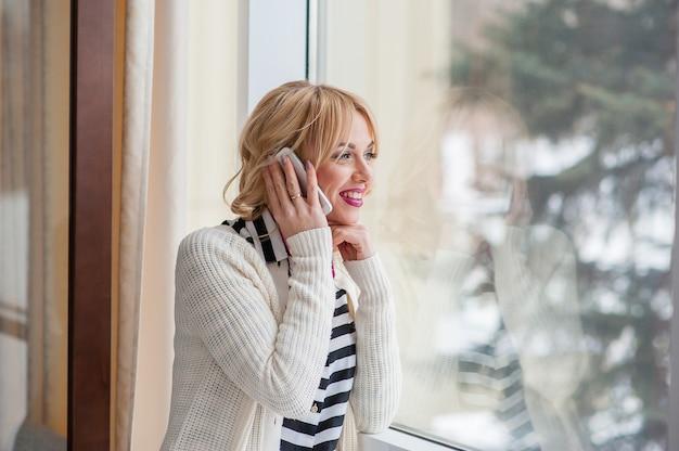 Красивая девушка разговаривает по телефону у окна