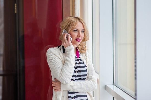 Pretty girl talking on the phone near a window, blonde