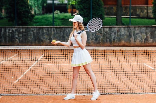 화창한 날 경기를 위해 준비된 예쁜 여자 테니스 선수.