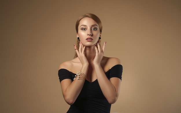 Pretty girl touching her face wearing black dress and golden jewelry