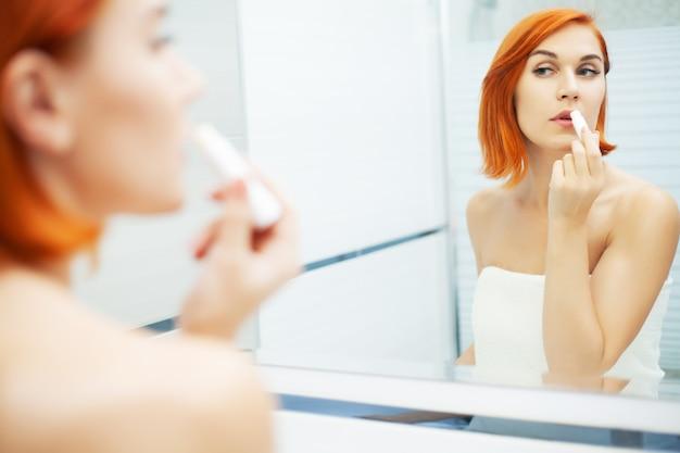 Красивая девушка использовать продукт ухода в светлой ванной комнате.