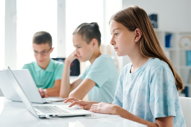 ラップトップを使用してかわいい女の子、学校の教室で机に座っている彼女のクラスメート