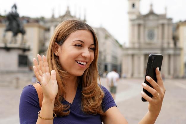 Красивая девушка по видеосвязи и приветствует с мобильного телефона во время ее путешествия по европе. молодая женщина-путешественница на городской площади делает селфи или делится своим опытом в видеоблоге, турин, италия.