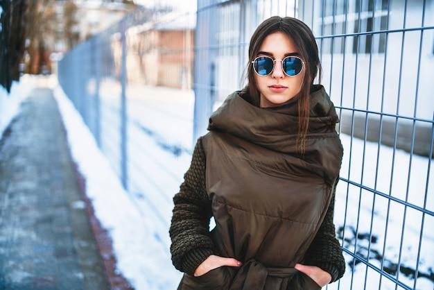 Милая девушка гуляя напольная на улице, зимнее время.