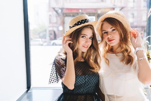 黒のエレガントな服装で興味のある友人とポーズをとってブレスレットと腕時計を身に着けているかわいい女の子