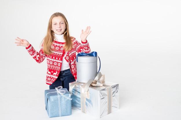 Красивая девушка в рождественском свитере сидит изолированно на белой поверхности