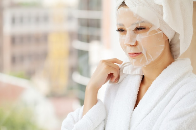 Pretty girl wearing face care mask at home.