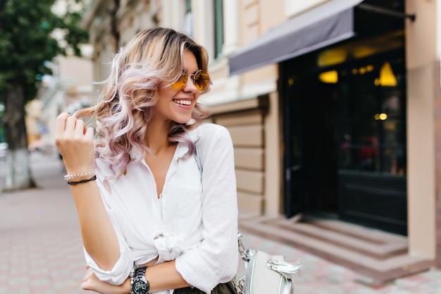Bella ragazza che indossa occhiali da sole e braccialetti che giocano con i suoi corti capelli ricci e sorridono per strada