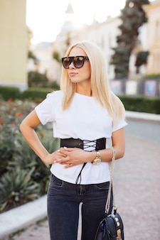 Pretty girl wearing sunglasses playing with her hair and smiling on the street. outdoor portrait of blonde young woman in the street.