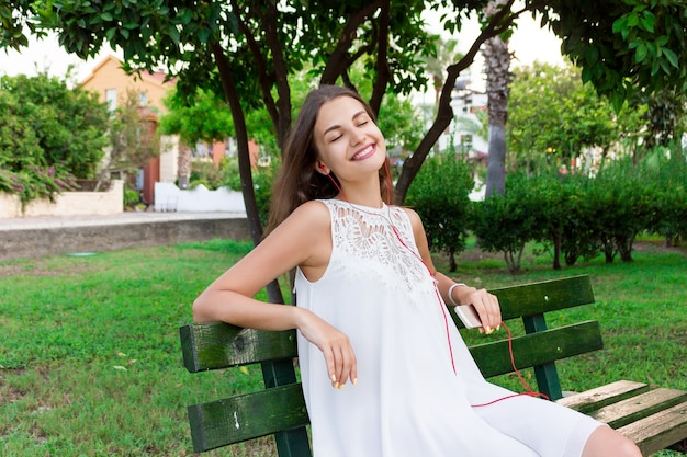 A pretty girl in a white dress is listening to her favourite song on the bench in the park. she enjoys and is having fun.