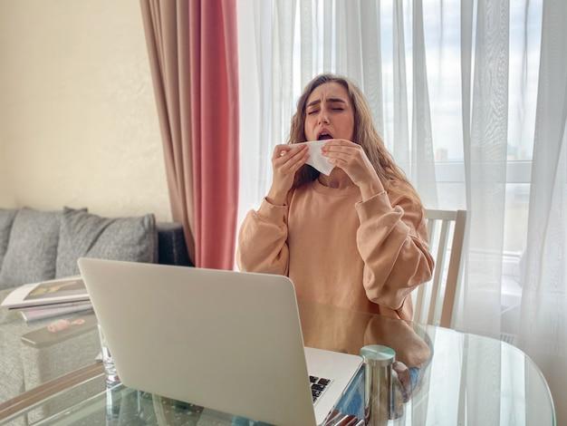 テーブルにラップトップを持ったかわいい女の子がコロナウイルスの発生に関するニュースを読む