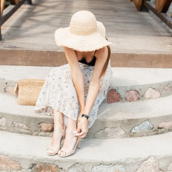 ファッショナブルなレースのランジェリーのビーチ麦わら帽子と織りハンドバッグとヴィンテージのスカートを持つかわいい女の子は靴を履く
