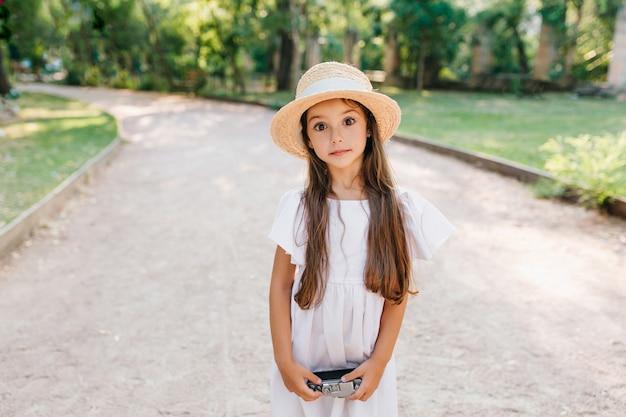 道路の真ん中に立ってカメラを持っている大きな驚きの目を持つかわいい女の子。夏の日に通りを歩いているわらのカンカン帽のスタイリッシュな女性の子供の屋外の肖像画。