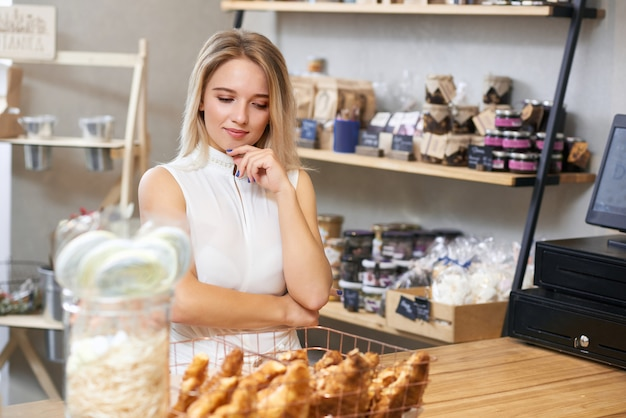 Pretty girl with blonde hair choosing croissants in local shop.