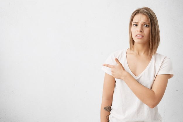 Pretty girl with bob hairstyle looking having scared or shocked facial expression, pointing her index finger sideways at white blank wall with copyspace