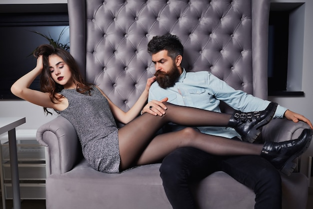 Pretty girl with brunette curly hair, red lipstick and handsome cute bearded man. fashion photo of beauty salon romance of sexy lovers. beautiful fashion couple in love