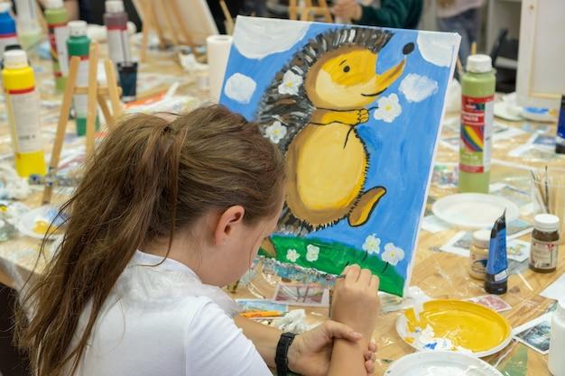 Красивая девушка с кистью в руке. творческая девочка-подросток рисует картину на мольберте. интерьер художественной школы для детей. концепция творчества и людей.