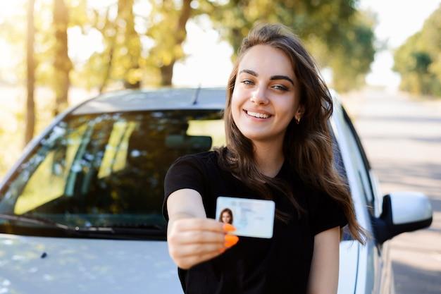 차 근처에 서서 운전 면허증을 전면에 보여주는 밝은 미소로 예쁜 소녀. 여자는 운전 시험에 합격 한 후 자신의 행복을 표현합니다.