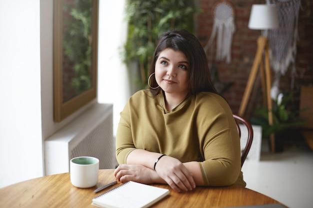 ぽっちゃりした頬と曲線美の体を持つかわいい女の子は、空白の空の日記とマグカップでコワーキングスペースに座って宿題をしています。カプチーノを飲んで、コピーブックにメモをとるスタイリッシュなプラスサイズの女性