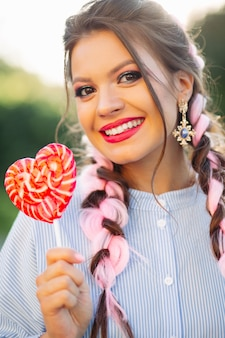 Pretty girl with colorful braids in blue dress, holding candy heart on stick.